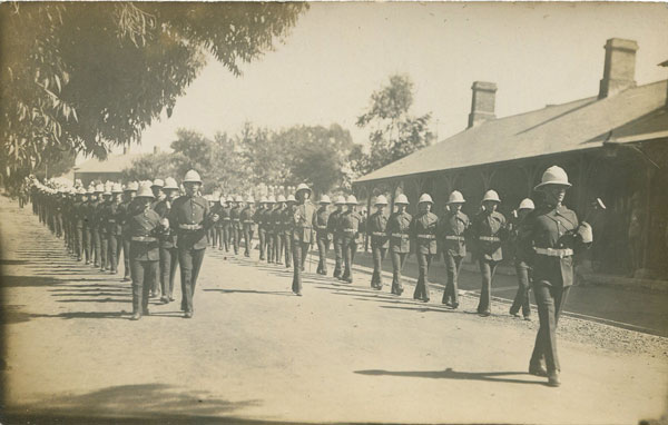ANON Military parade with Wynberg railway station in background.